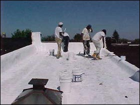 Figure 5. Workers apply a cool roof coating on a rowhouse in Baltimore, Maryland. (Source: EPA)